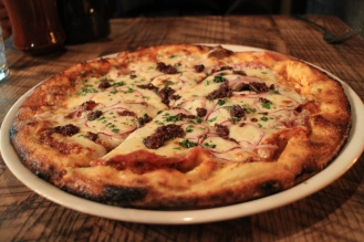 Woodfired pizza with Spanish chorizo, sopressata, red onion and olive tapenade