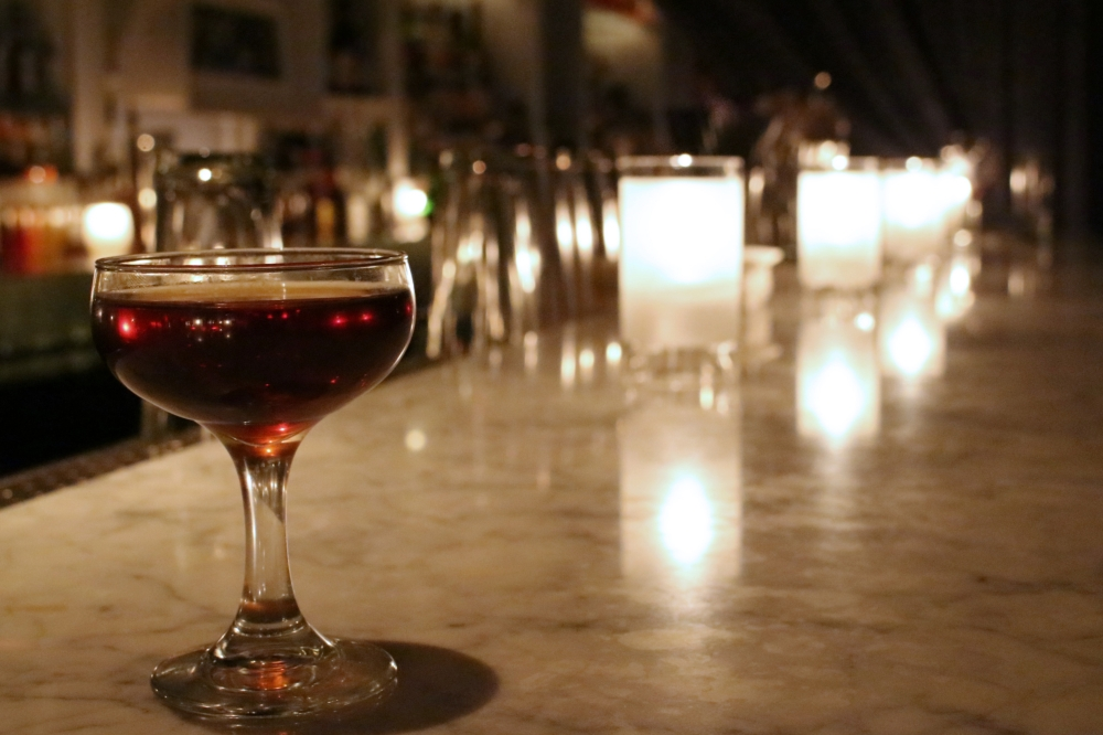 A delicious stirred rum cocktail lit by candles